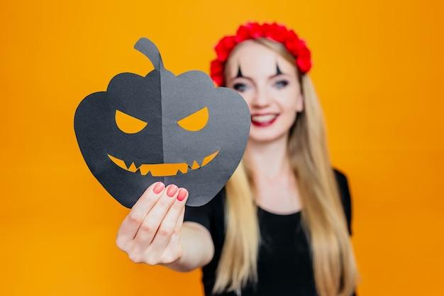 Ragazza felice in costume di halloween che tiene la zucca e isolata sull'arancio