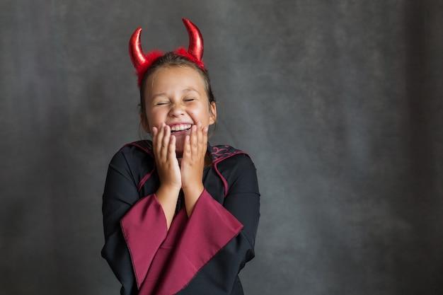 Ragazza felice in costume di halloween maledetto sul muro grigio