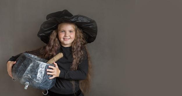 La ragazza felice in costume della strega di halloween prepara una pozione