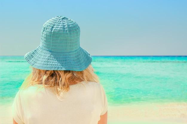 Ragazza felice in cappello in riva al mare sulla natura di cipro