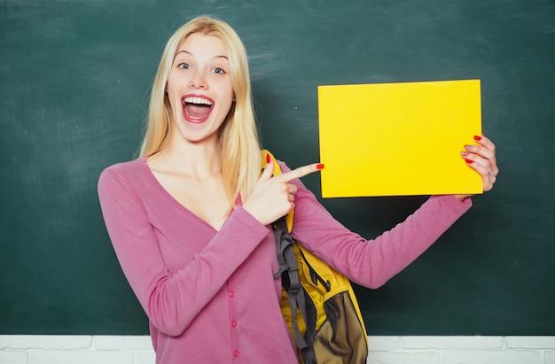 Ragazza felice che tiene il libro e che guarda l'obbiettivo mentre levandosi in piedi in aula