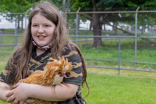 Ragazza felice che tiene un pollo padovana carino fuori.