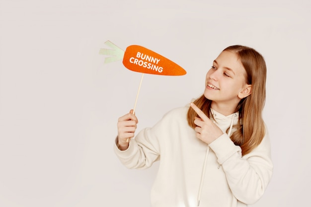 Una ragazza felice tiene una carota con la scritta bunny crossing in mano