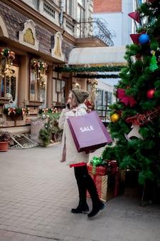 La ragazza felice tiene i sacchetti di carta con il simbolo della vendita nei negozi con le vendite a natale