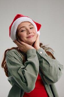 Ragazza felice in cappello di vacanze che tocca il fronte con le mani e il modello del partito divertente