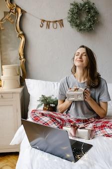 La ragazza felice è seduta davanti allo schermo di un computer con una confezione regalo tra le mani a casa Foto Premium