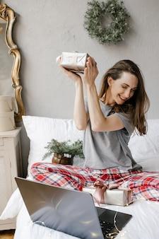 La ragazza felice è seduta davanti allo schermo di un computer con una confezione regalo tra le mani a casa