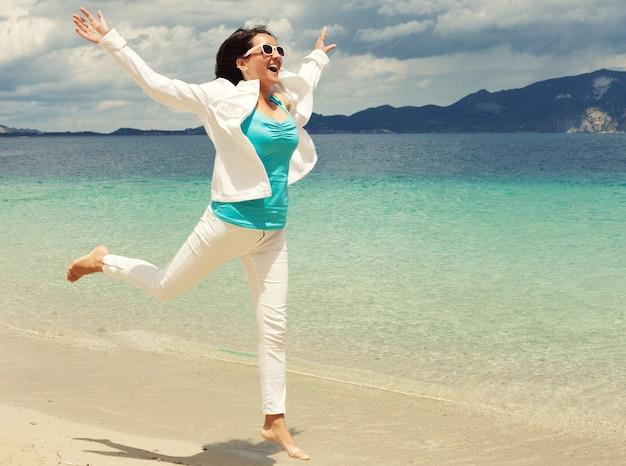 Ragazza felice che salta sulla spiaggia, vacanze estive