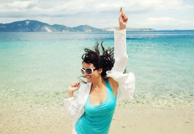 Ragazza felice che salta sulla spiaggia