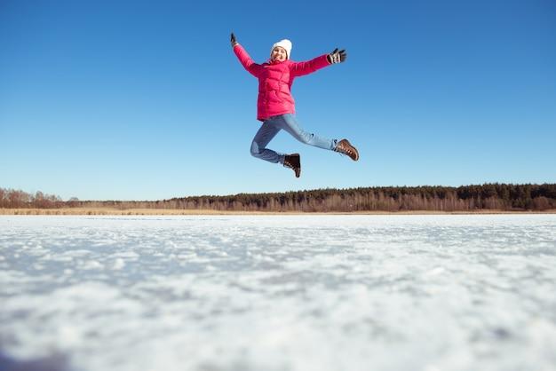 Ragazza felice che salta sopra il cielo blu e la neve sullo sfondo