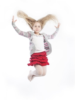 La ragazza felice salta su uno sfondo bianco