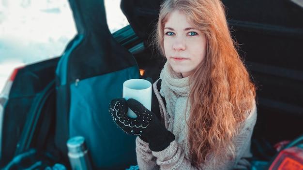 Ragazza felice in vestiti lavorati a maglia, sciarpa e plaid che si siede sul camion della macchina nella foresta di inverno con una tazza di tè o caffè caldo