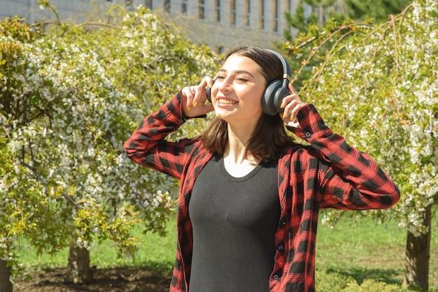 Ragazza felice che ascolta la musica in cuffia e balla nel parco