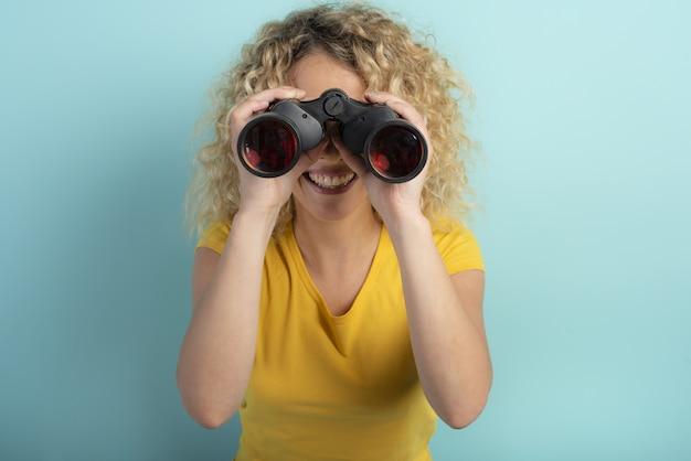 La ragazza felice osserva con qualcosa binoculare. parete ciano