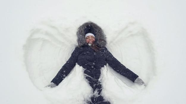 Ragazza felice che si trova su una neve e mostra l'angelo.