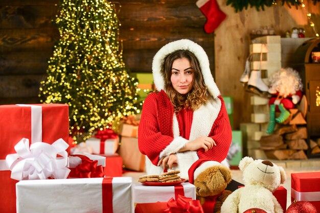 La ragazza felice ha fatto i biscotti per santa. santa donna sente la felicità nel nuovo anno. ragazza santa tra i regali di natale e la scatola dei regali. acquisti del venerdì nero. festa in casa con biscotto di natale.