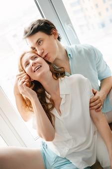 Ragazza felice e uomo che si abbracciano vicino alla finestra in casa. vestiti bianchi e blu. san valentino.