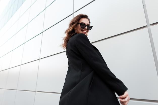 Modello di ragazza felice in outwear nero di moda cammina per strada