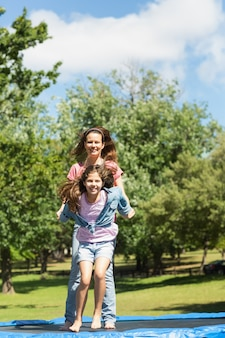 Ragazza felice e madre che saltano su sul trampolino nel parco