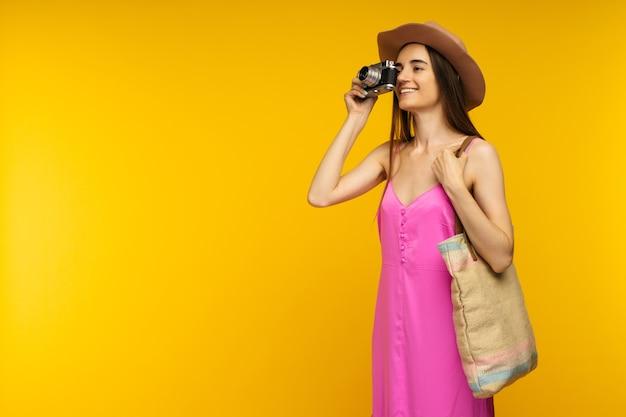Ragazza felice in un vestito rosa e occhiali da sole tenendo la fotocamera su uno sfondo giallo