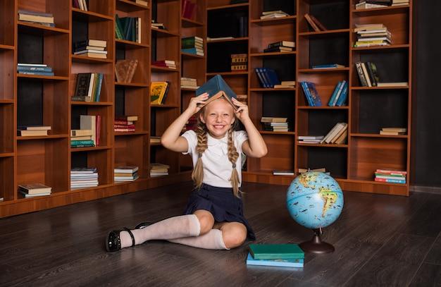 Allievo della ragazza felice in uniforme scolastica che si siede con un libro sulla sua testa e che ride in classe