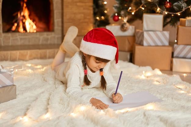 Ragazza felice in cappello rosso di natale che scrive la lettera a babbo natale o che disegna l'immagine