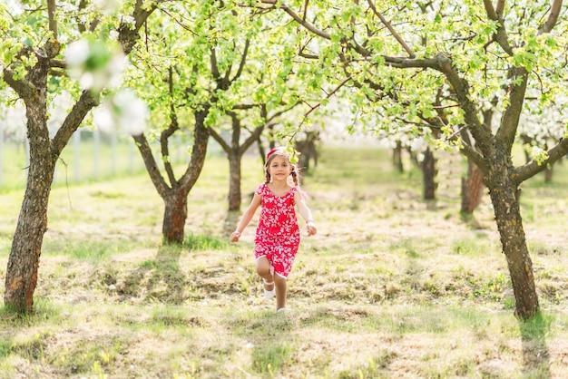 La ragazza felice nelle prendisole rosse funziona in un giardino di fioritura
