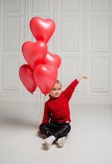 Felice ragazza in maglione rosso e jeans in pelle seduto e tenendo palloncini rossi su sfondo bianco con spazio per il testo