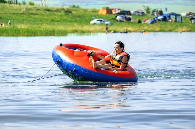 Ragazza felice cavalca in estate su un panino dietro una barca sul lago shira