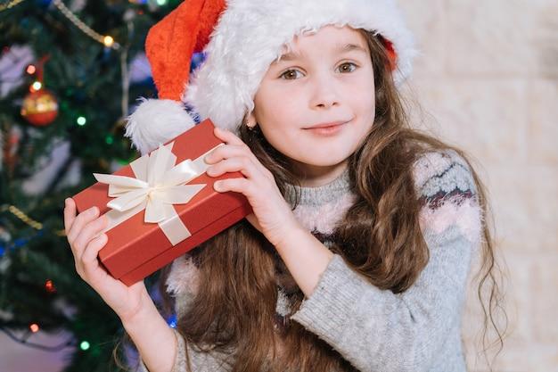 Ragazza felice in cappello della santa che tiene il contenitore di regalo rosso per scoprire cosa c'è dentro.