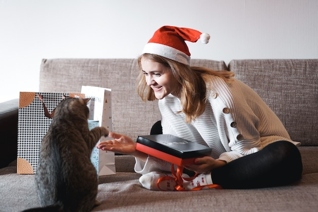 Ragazza felice in cappello della santa che apre il contenitore di regalo di natale e gioca con il gatto.