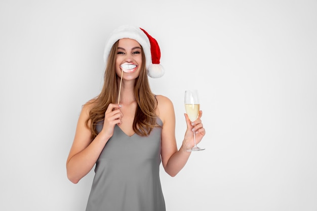 La ragazza felice con il cappello di babbo natale indossa un sorriso finto tiene in mano un bicchiere di champagne per la festa di capodanno