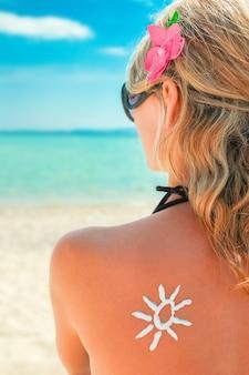 Ragazza felice sul mare con una foto del sole sulla schiena
