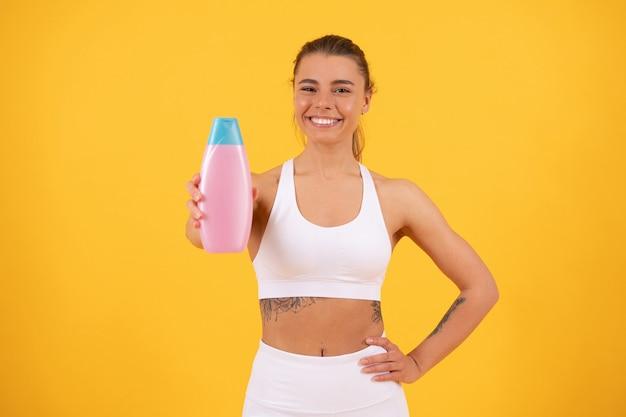 Ragazza felice che mostra una bottiglia di balsamo per shampoo per capelli o lozione per il corpo per la cura della pelle e il bagno, abitudine quotidiana.
