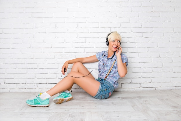 Felice ragazza seduta sul pavimento e ascolta la musica in cuffia