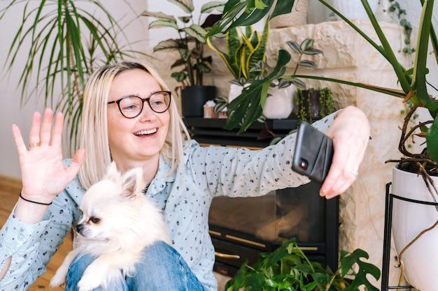 Ragazza felice che si siede a casa cucina e che tiene videocall. giovane donna che per mezzo dello smartphone per la videochiamata con l'amico o la famiglia. webinar di registrazione di vlogger. donna che osserva macchina fotografica e mani d'ondeggiamento di saluto