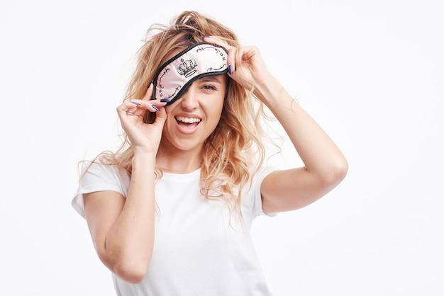La ragazza felice in maschera per dormire e pigiama bianco si è svegliata la mattina presto e guardando la telecamera e sorridente.