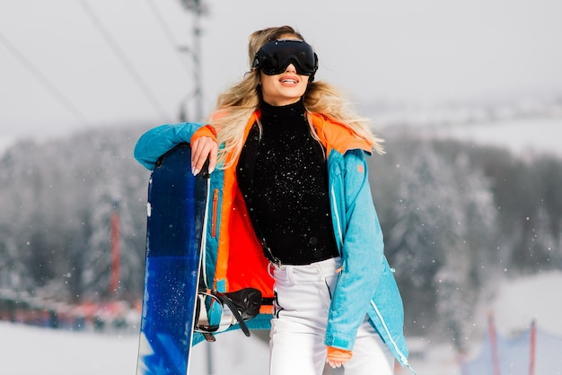 Snowboarder ragazza felice in posa in occhiali da sole con uno snowboard