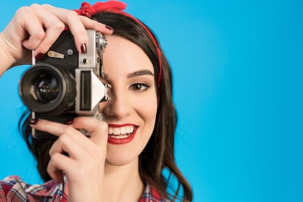 La ragazza felice scatta una foto con una fotocamera retrò sullo sfondo blu