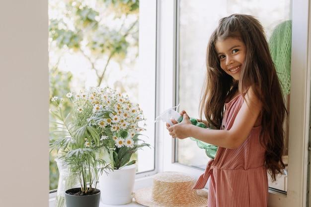 Ragazza felice che si prende cura delle piante d'appartamento a casa vestita con un elegante abito rosa polveroso giardinaggio domestico