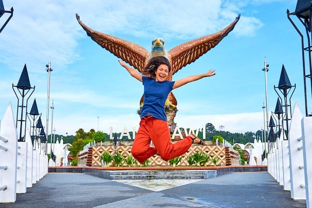 Turista felice della ragazza che posa accanto alla scultura di un'aquila rossa che spande le sue ali. località turistica popolare sull'isola di langkawi