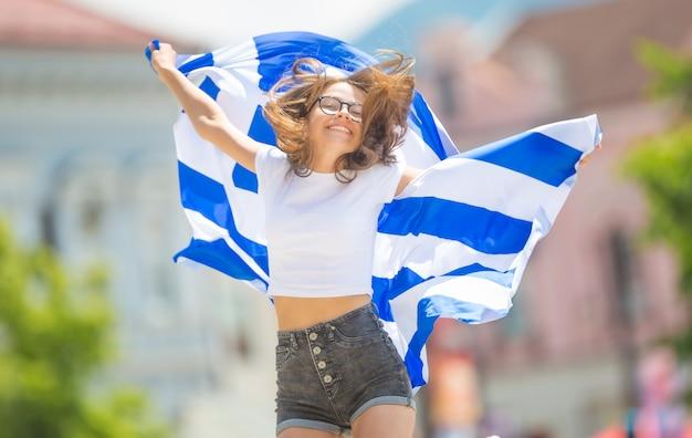 Turista felice della ragazza che cammina nella via con la bandiera della grecia.