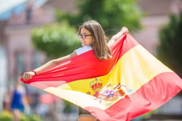 Turista felice della ragazza che cammina nella via con la bandiera spagnola