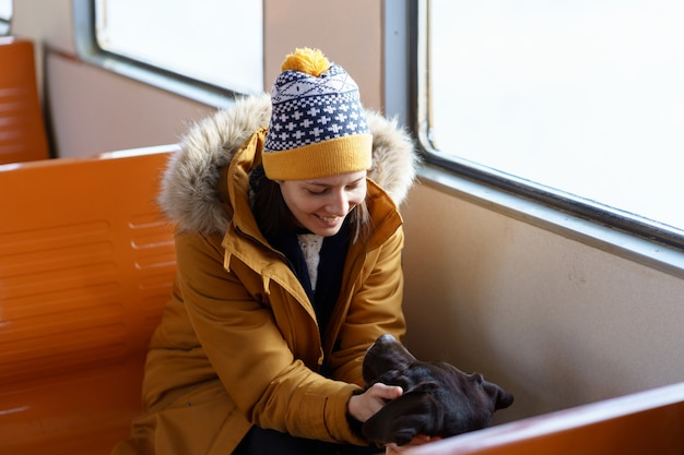La ragazza felice indossa abiti invernali seduto in treno locale a parlare con il suo adorabile cane che viaggiano insieme