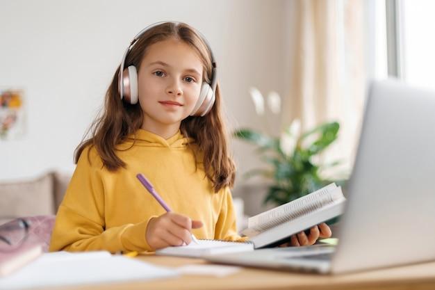 Felice ragazza che indossa le cuffie, guardando la fotocamera, facendo il lavoro a casa utilizzando laptop e internet.