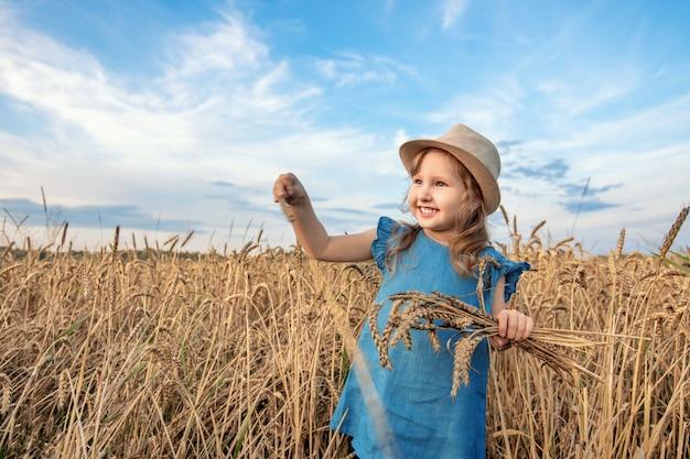 Ragazza felice nel campo di frumento in serata estiva calda e soleggiata.
