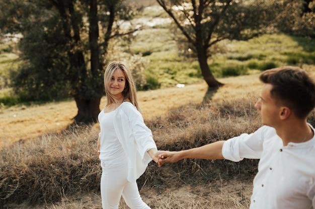 Ragazza felice in vestiti bianchi nella tenuta dell'uomo a mano nel parco. seguimi.