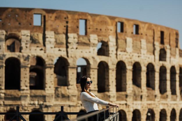 Ragazza felice in camicia bianca con gli occhiali sorridente e ammira il colosseo di roma.