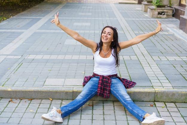 La ragazza felice in maglietta bianca, jeans blu e scarpe da ginnastica bianche si siede sul marciapiede nel parco durante il giorno. allegro allarga le mani di lato con i palmi, espressione emotiva sul viso