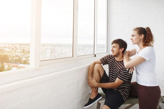Ragazza felice in maglietta bianca e ragazzo con la barba, coppia carina guardando fuori dalla finestra nella loro nuova casa
